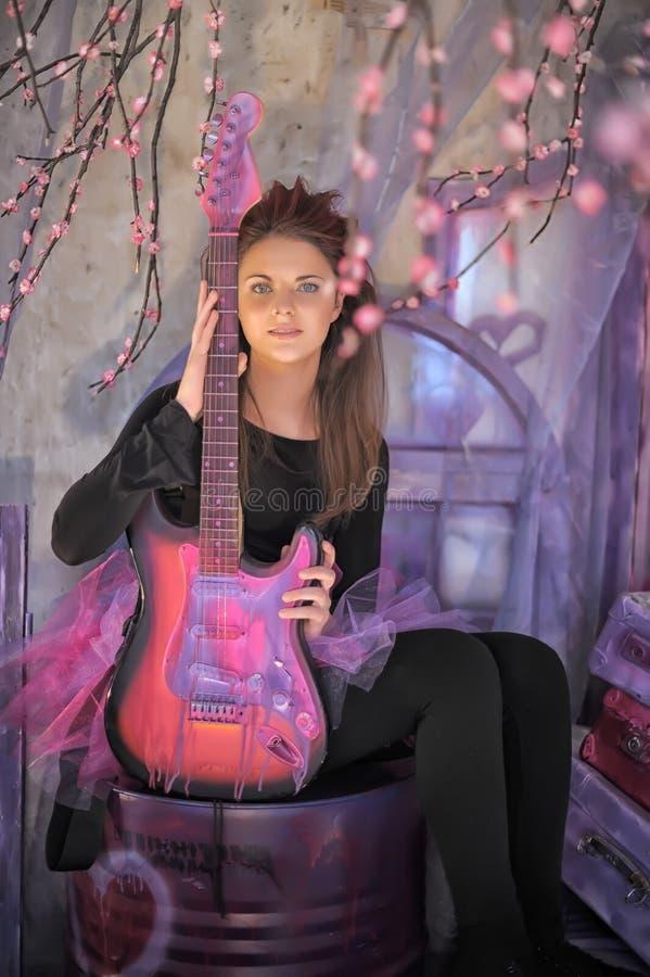 Chica joven hermosa con la guitarra eléctrica fotografía de archivo libre de regalías