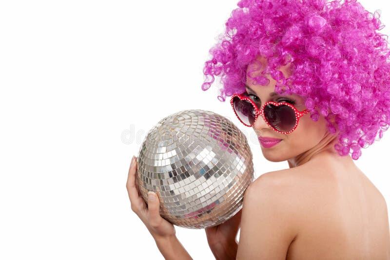 Chica joven hermosa con la peluca rosada que sostiene la bola de discoteca, aislada foto de archivo