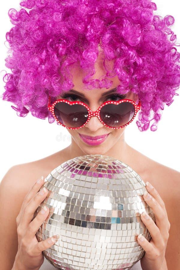 Chica joven hermosa con la peluca rosada que sostiene la bola de discoteca, aislada imagen de archivo