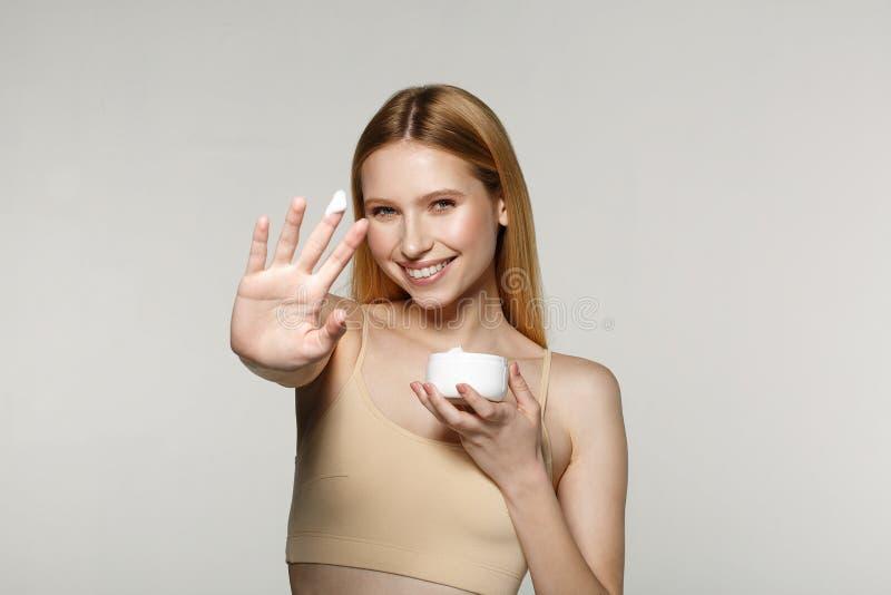 Chica joven hermosa con la piel perfecta que sostiene y que presenta el producto poner crema del tubo foto de archivo libre de regalías
