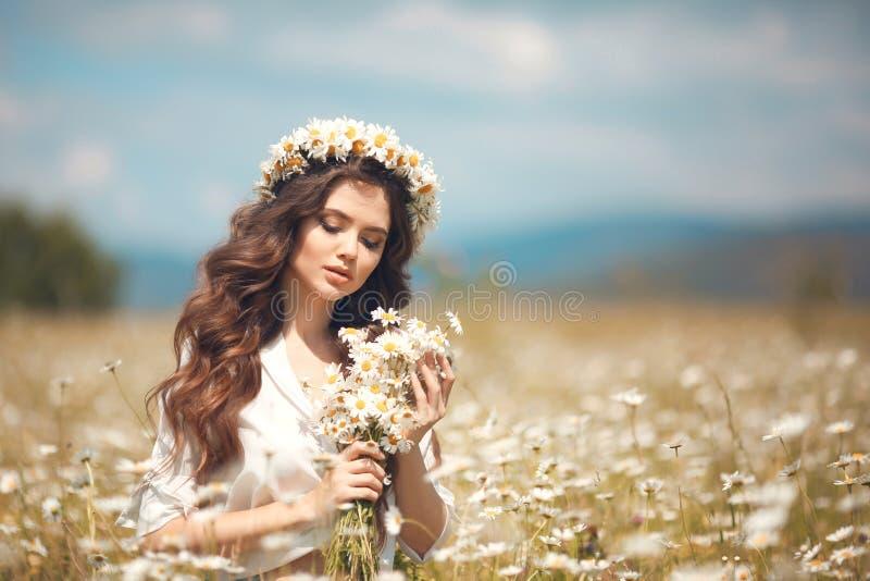Chica joven hermosa con las flores que goza en campo de la manzanilla Mujer morena feliz despreocupada con la guirnalda en el pel fotografía de archivo libre de regalías