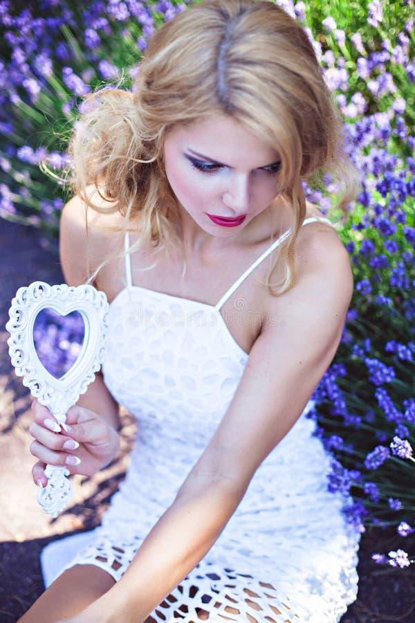 Chica joven hermosa con lavanda floreciente cercana del espejo imágenes de archivo libres de regalías