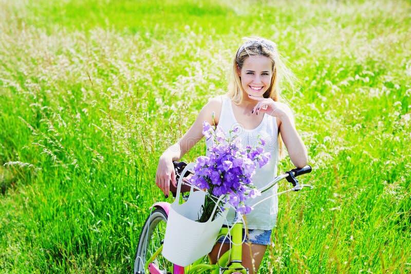 Chica joven hermosa con su bici del crucero imagenes de archivo