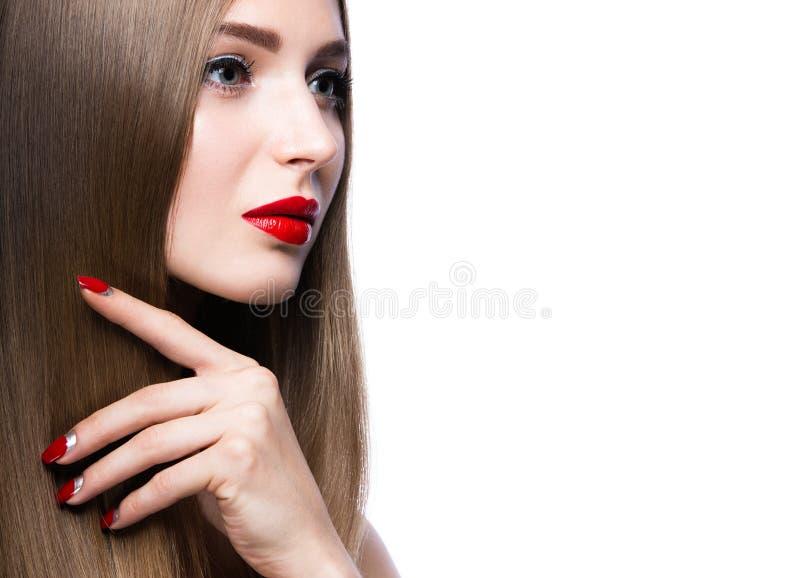 Chica joven hermosa con un maquillaje brillante y clavos rojos fotos de archivo libres de regalías