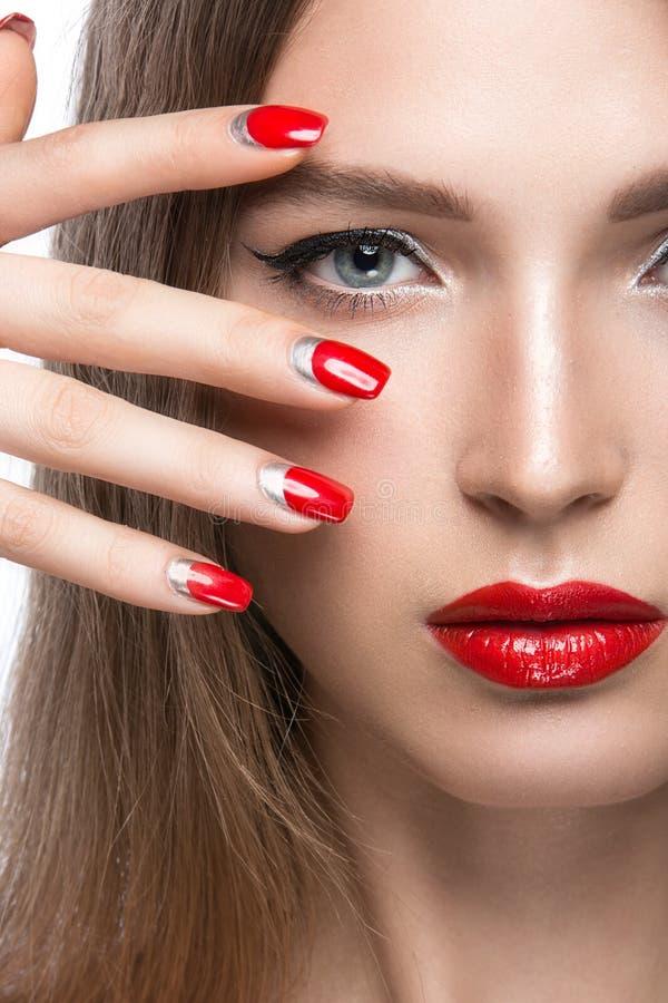 Chica joven hermosa con un maquillaje brillante y clavos rojos Cara de la belleza imagenes de archivo