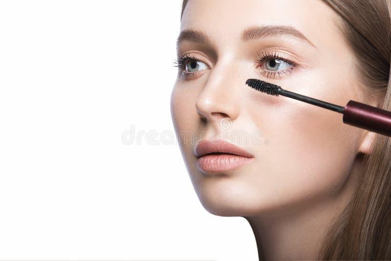 Chica joven hermosa con un maquillaje natural ligero y herramientas de la belleza a disposición imagen de archivo
