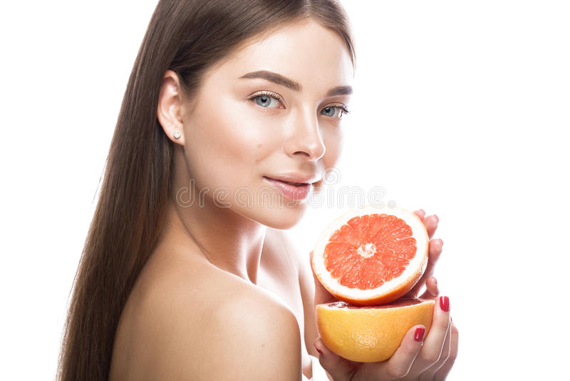 Chica joven hermosa con un maquillaje natural ligero y piel perfecta con el pomelo en su mano Cara de la belleza imagen de archivo