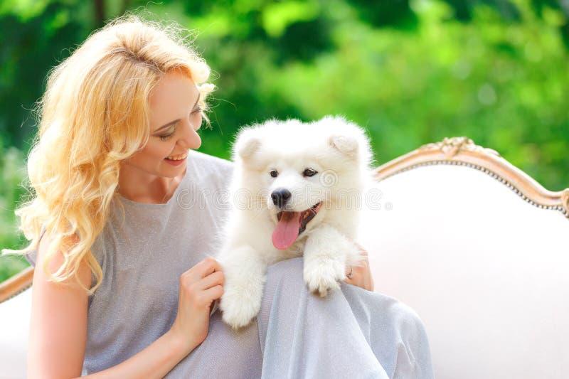 Chica joven hermosa con un perrito blanco en sus brazos en un sofá retro en un jardín del verano imagenes de archivo