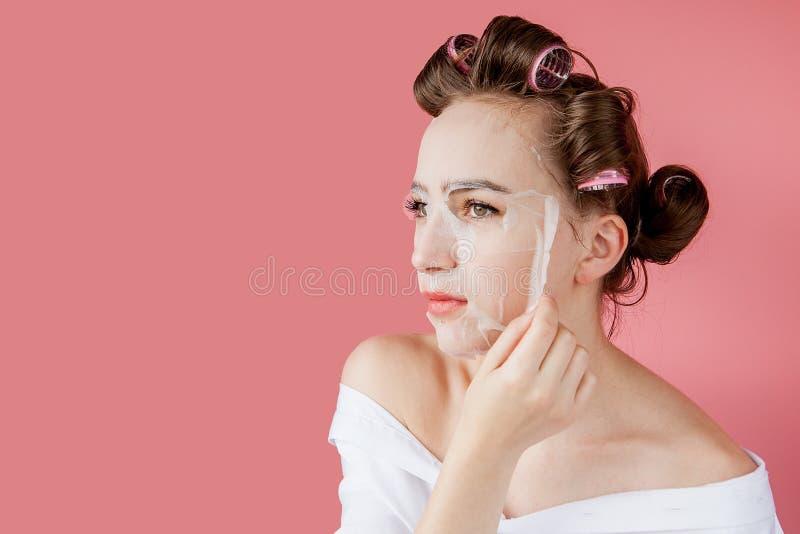 Chica joven hermosa con una máscara y los bigudíes que tocan su cara fotos de archivo libres de regalías