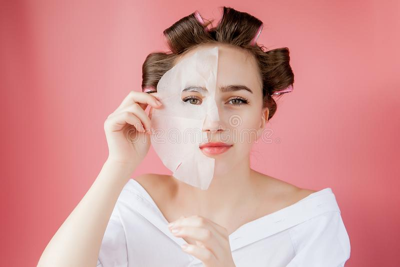 Chica joven hermosa con una máscara y los bigudíes que tocan su cara fotografía de archivo