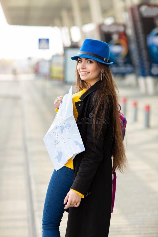 Chica joven hermosa con una mochila detr?s de su hombro que sostiene un mapa, en la calle cerca del aeropuerto imagen de archivo