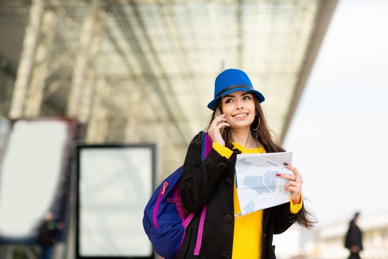 Chica joven hermosa con una mochila y un sombrero azul, hablando en m?vil en la calle cerca del aeropuerto fotografía de archivo libre de regalías