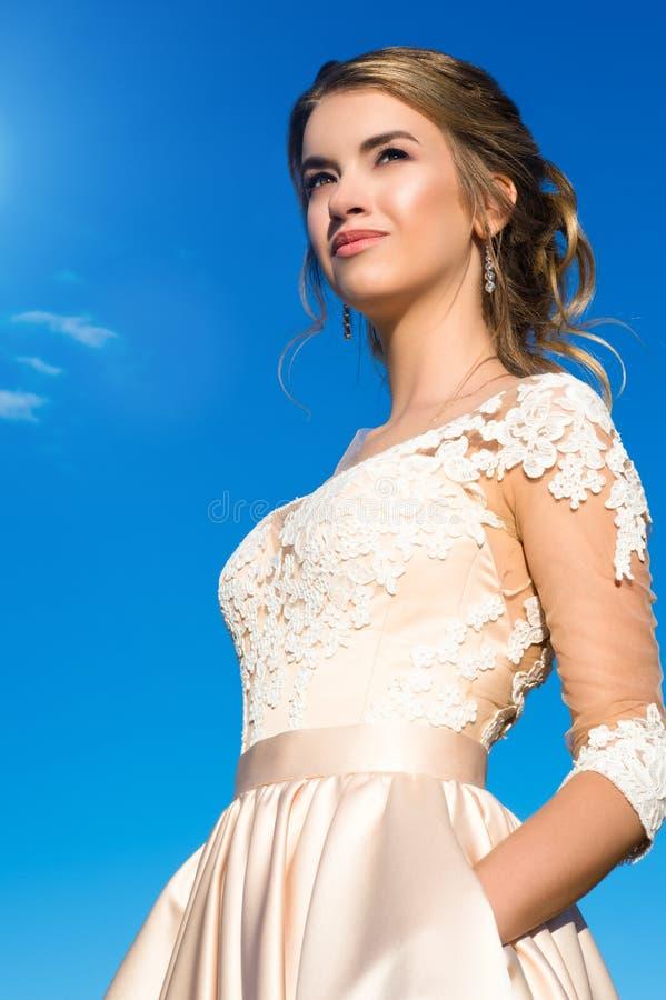 Chica joven hermosa del retrato en vestido beige en el cielo azul del fondo imagen de archivo