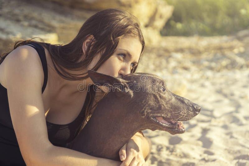 Chica joven hermosa del retrato que besa su xoloitzcuintle de la raza del perro, verano en una playa de la arena en la puesta del imagen de archivo