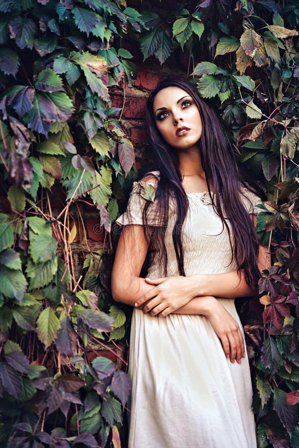 Chica joven hermosa en el vestido blanco que se coloca entre las hojas coloridas imágenes de archivo libres de regalías