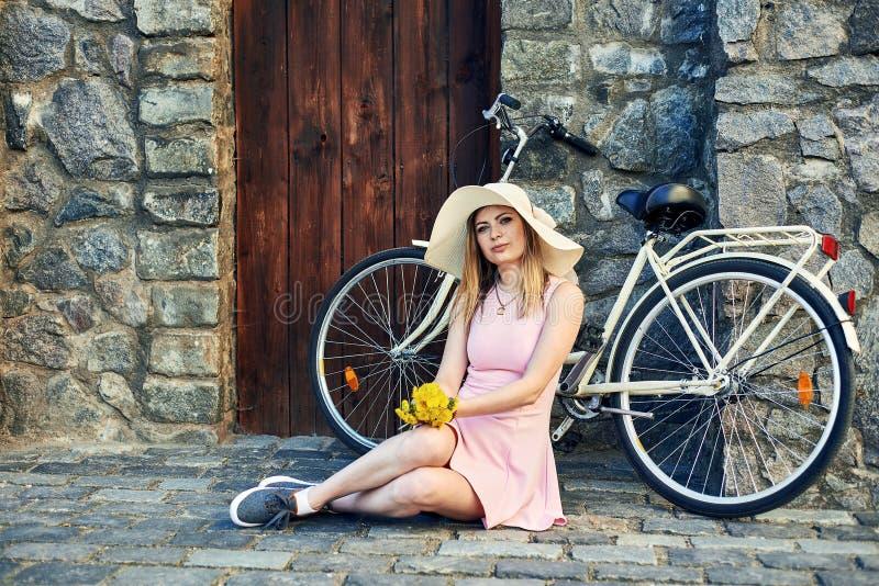 Chica joven hermosa en el vestido rosado, sombrero de paja que presenta el retrato que se sienta en el camino de piedra en ciudad fotografía de archivo