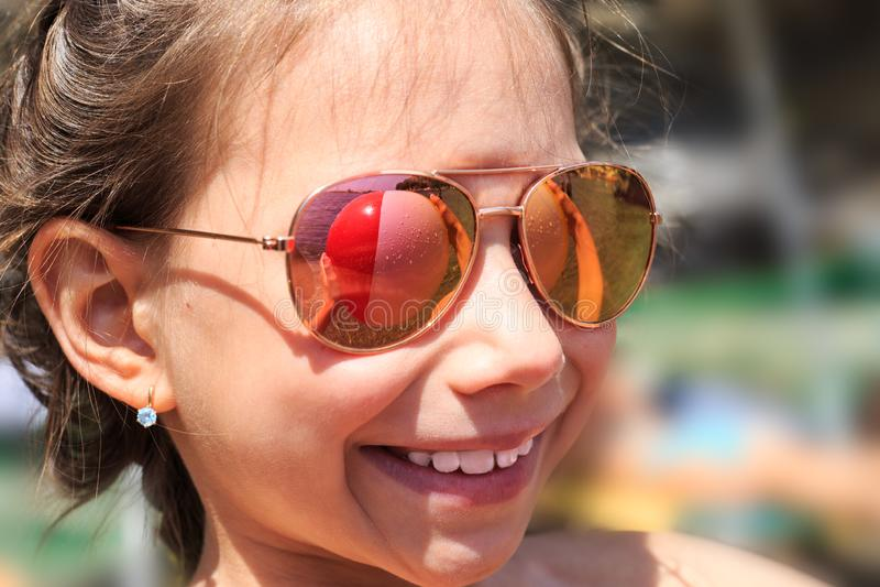 Chica joven hermosa en gafas de sol con el rerlection de la pelota de playa imagenes de archivo
