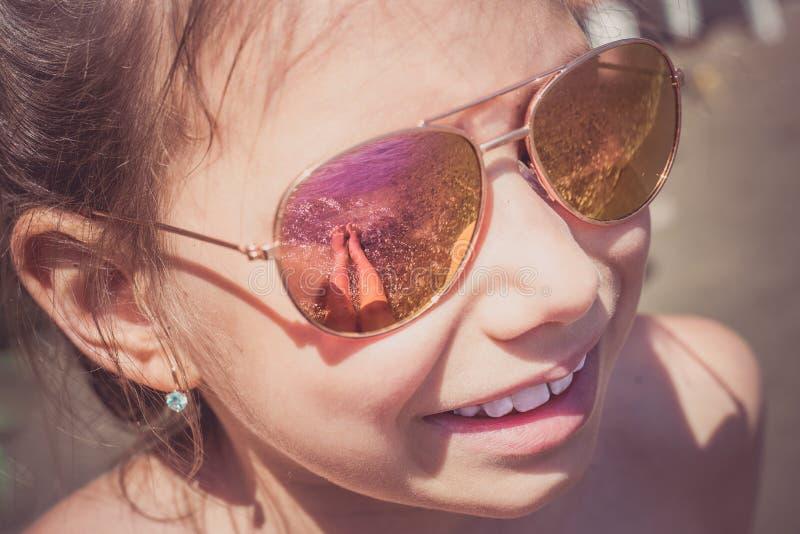 Chica joven hermosa en gafas de sol con las piernas en la reflexión de la playa foto de archivo libre de regalías
