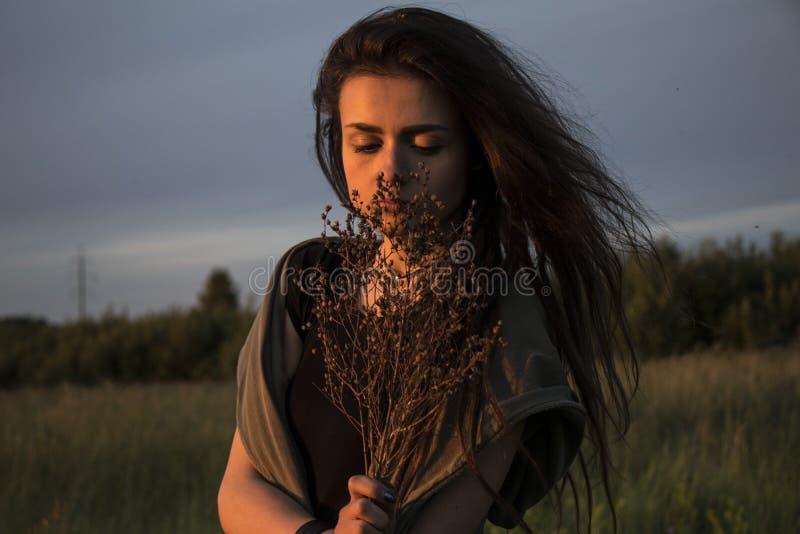 Chica joven hermosa en la chaqueta que se acuesta en hierba imagen de archivo