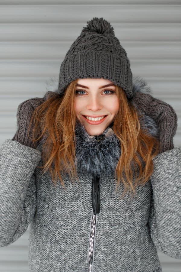 Chica joven hermosa en los géneros de punto del invierno que presentan cerca de una pared del metal foto de archivo