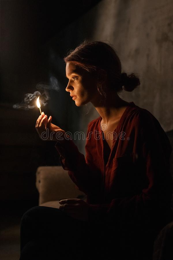 Chica joven hermosa en luces rojas de la camisa para arriba su cara bonita con el partido que se sienta en sitio oscuro y que sos fotografía de archivo libre de regalías