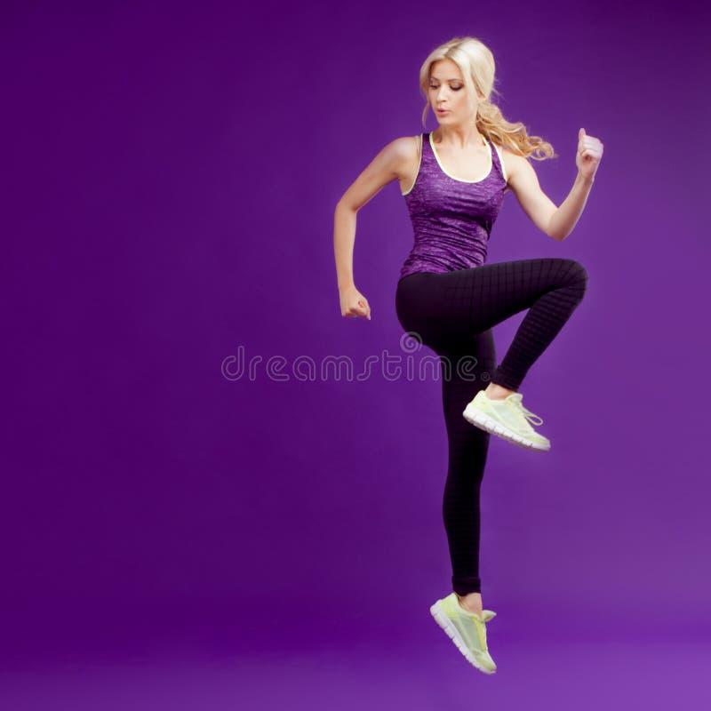 Chica joven hermosa en un corredor de la actitud Fondo del estudio, púrpura imagen de archivo libre de regalías
