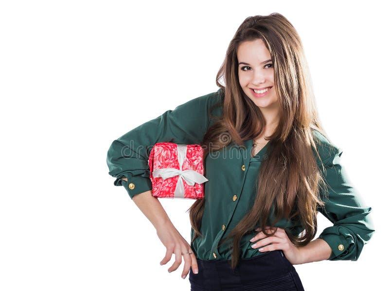 Chica joven hermosa en un fondo blanco que sostiene una caja con un regalo sonrisas fotografía de archivo libre de regalías