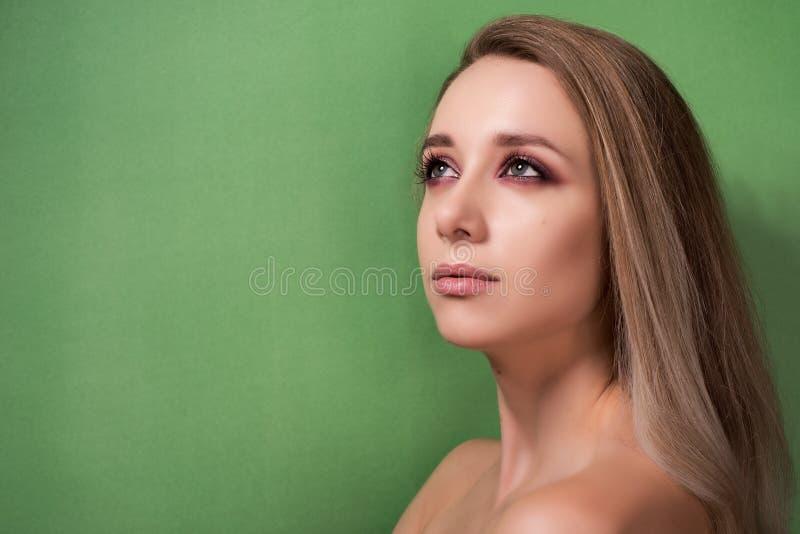 Chica joven hermosa en un fondo verde fotos de archivo