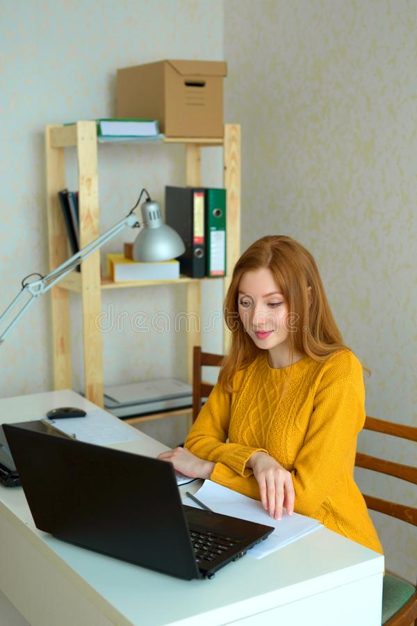 Chica joven hermosa en un suéter amarillo y un pelo rojo imágenes de archivo libres de regalías
