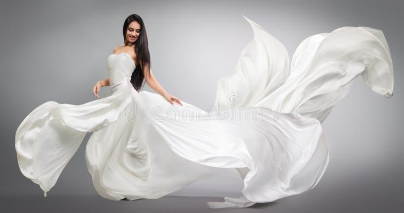 Chica joven hermosa en vestido blanco que vuela Tela que fluye Vuelo blanco ligero del paño imagen de archivo