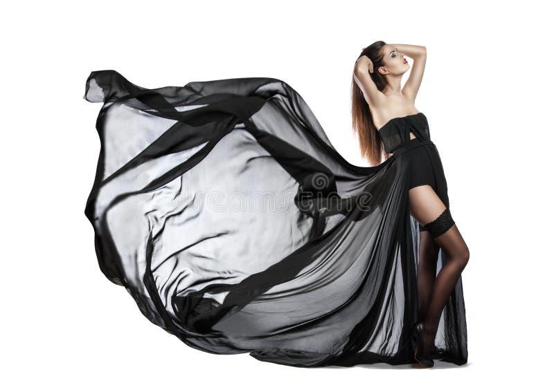 Chica joven hermosa en volar el vestido negro Tela que fluye imagen de archivo