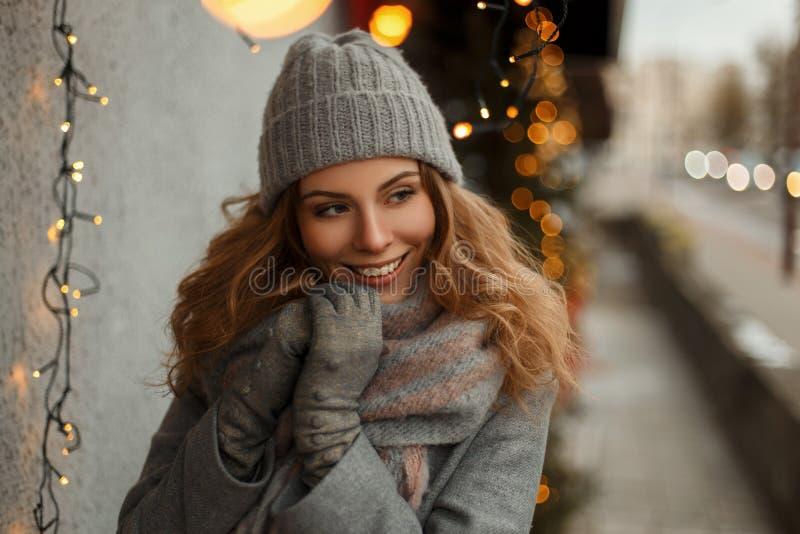 Chica joven hermosa feliz con una sonrisa excelente en géneros de punto imagen de archivo