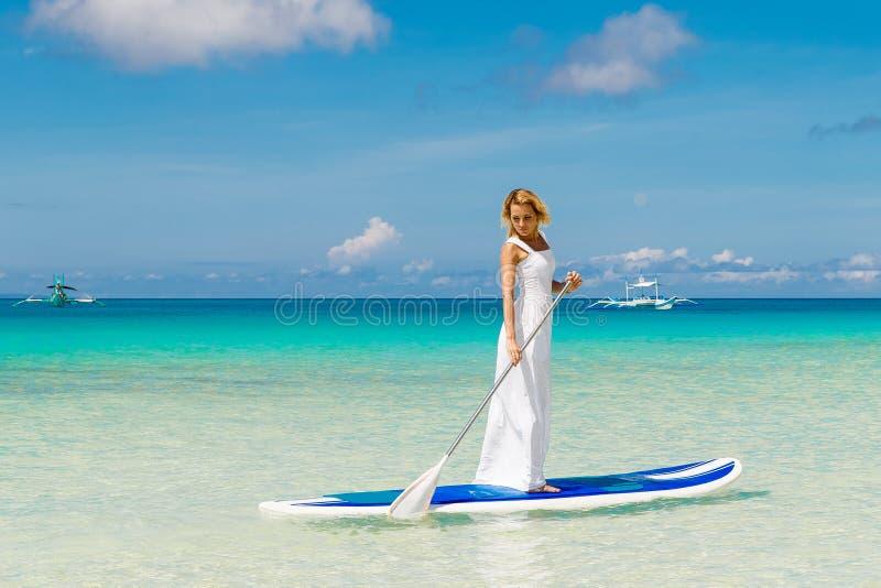 Chica joven hermosa feliz en un vestido blanco con el tablero de paleta encendido imagenes de archivo