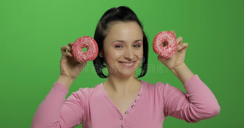Chica joven hermosa feliz que plantea y que se divierte con los anillos de espuma Llave de la croma fotografía de archivo libre de regalías
