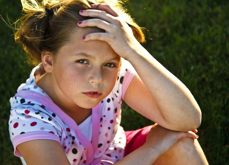 Chica joven hermosa infeliz en la hierba foto de archivo libre de regalías