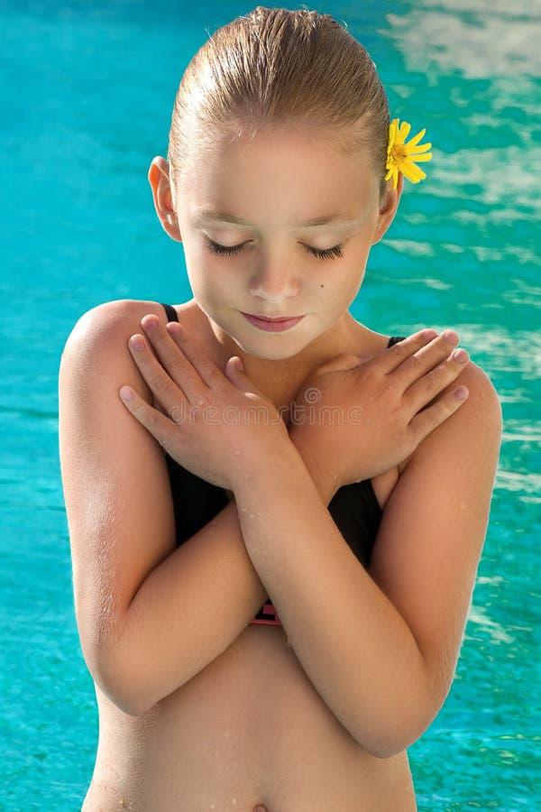 Chica joven hermosa, pequeña princesa con el pelo rubio con un peinado del bollo y con una flor amarilla en el pelo, colocándose  imagenes de archivo