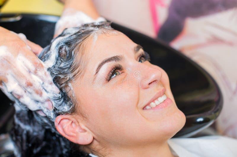 Chica joven hermosa que goza del pelo que se lava en salón de la peluquería imágenes de archivo libres de regalías