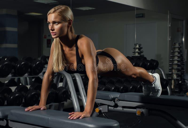 Chica joven hermosa que hace ejercicios en club de fitness en los bancos imagen de archivo