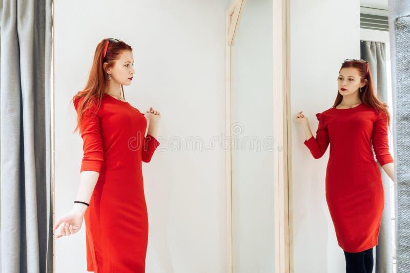 Chica joven hermosa que intenta en un vestido rojo en la tienda Mujer bonita que presenta cerca del capricho imagenes de archivo