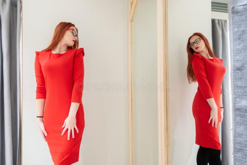 Chica joven hermosa que intenta en un vestido rojo en la tienda Mujer bonita que presenta cerca del capricho foto de archivo
