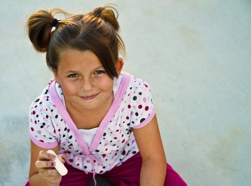 Chica joven hermosa que juega con tiza del sidewallk. fotografía de archivo