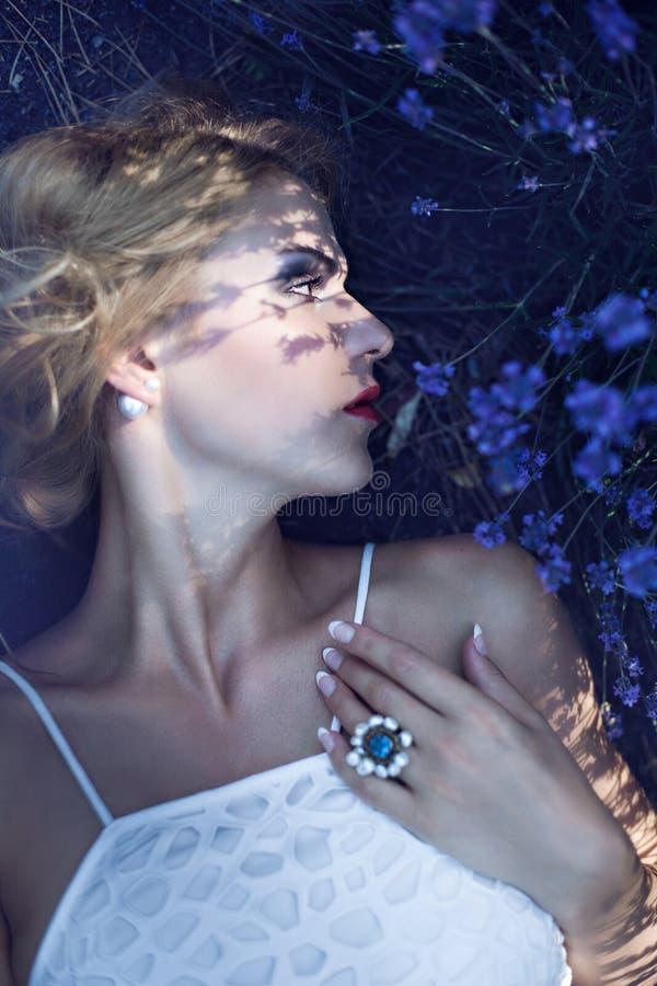Chica joven hermosa que miente cerca de la lavanda floreciente imagen de archivo