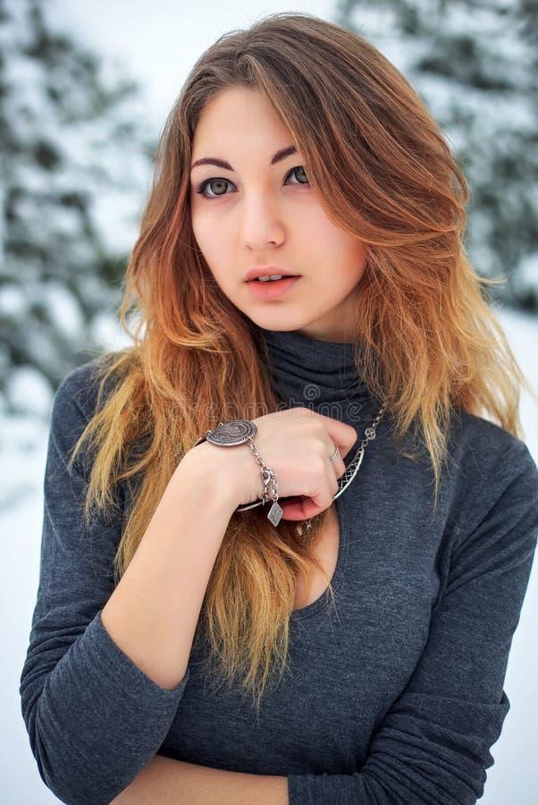 Chica joven hermosa que presenta en el invierno en bosque frío imágenes de archivo libres de regalías
