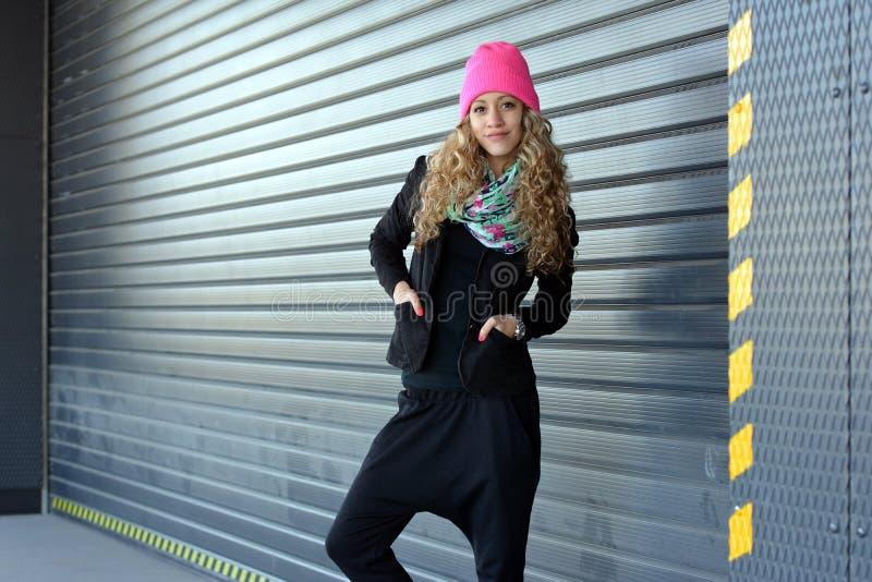 Chica joven hermosa que presenta para las puertas del garaje fotografía de archivo