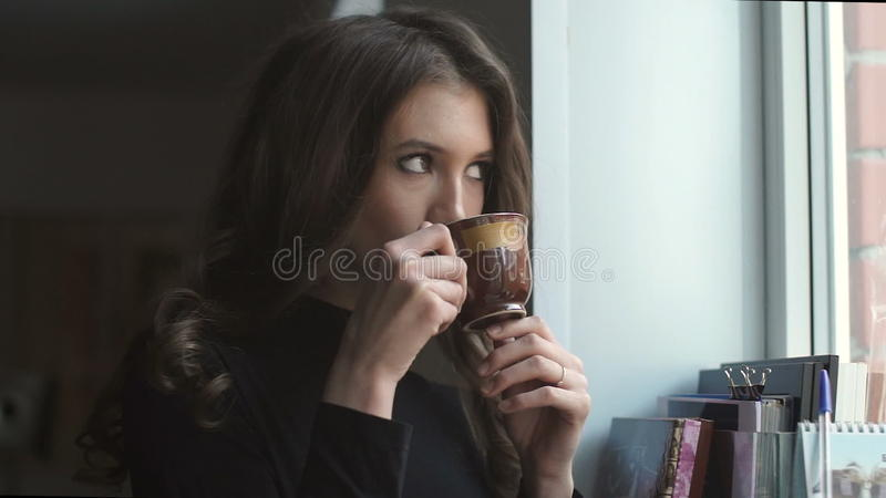Chica joven hermosa que se coloca al lado de la ventana y del coffe de consumición metrajes