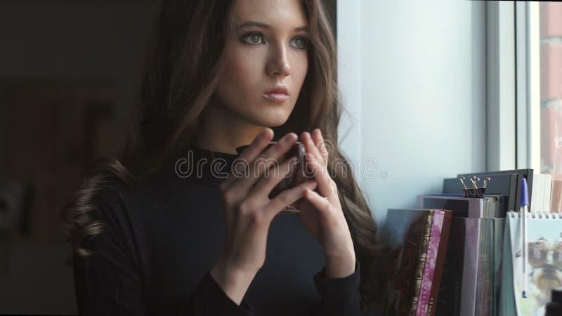 Chica joven hermosa que se coloca al lado de la ventana y del coffe de consumición almacen de metraje de vídeo