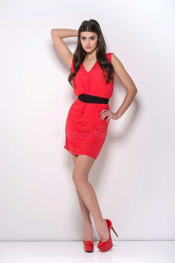 Chica joven hermosa que se coloca en vestido rojo foto de archivo libre de regalías
