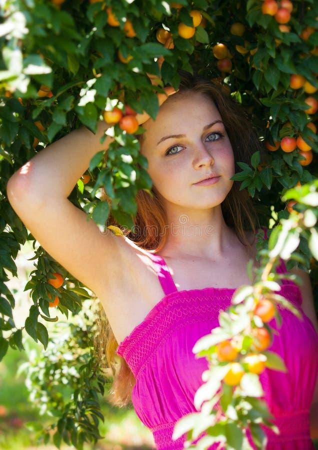 Chica joven hermosa que se relaja en jardín del árbol de ciruelo imagenes de archivo