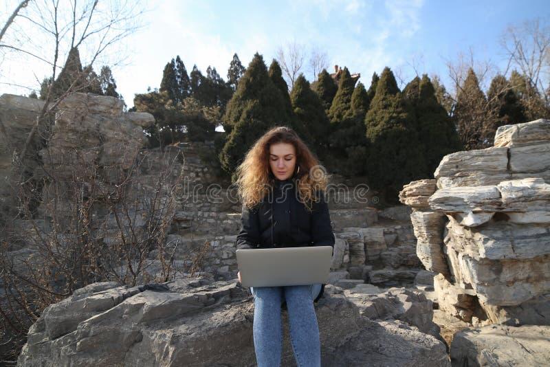 Chica joven hermosa que se sienta con un ordenador portátil en el parque en un fondo de montañas Las posibilidades son sin fin en fotografía de archivo