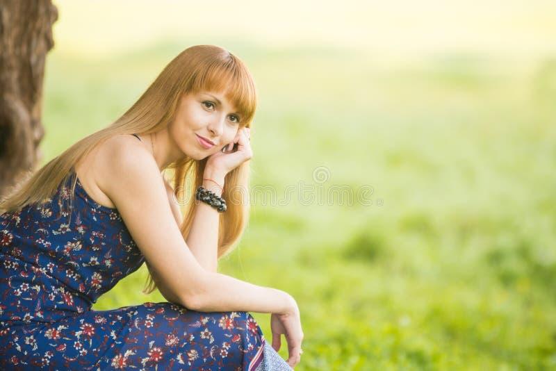 Chica joven hermosa que se sienta contra un árbol en el fondo de la hierba verde borrosa y de las miradas en la distancia foto de archivo libre de regalías